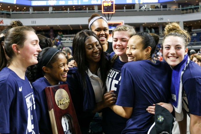 UConn's Azura Stevens (center), Saniya Chong (second from right), and Katie Lou Samuelson (right) crash the freshmen's photo with the trophy.