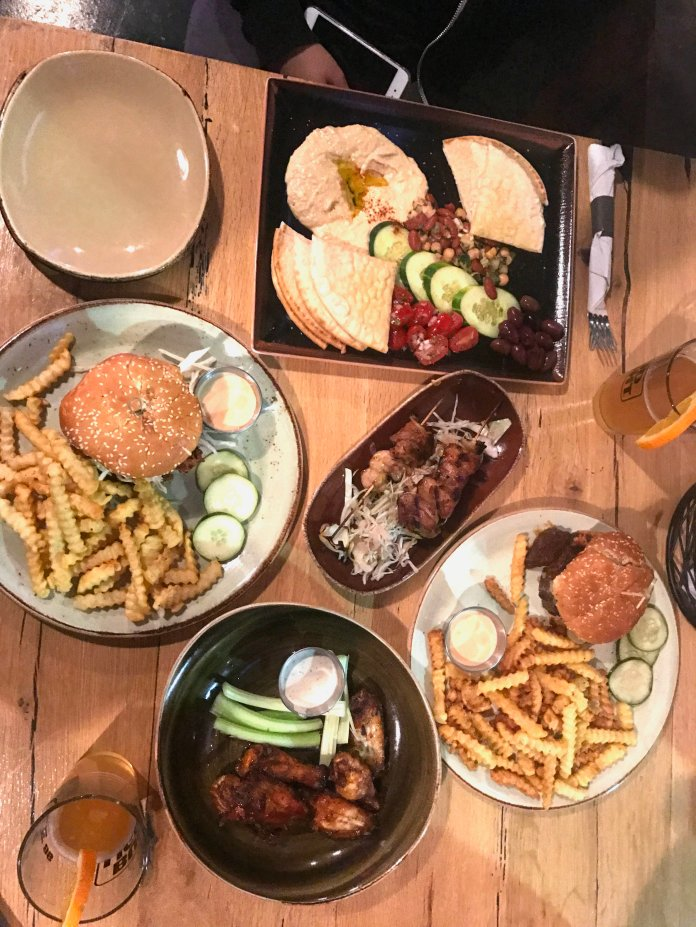 A sampling of the initial Grille 86 menu: The hummus platter, a pair of teriyaki skewers, Jordan Reed chili burger, crispy chicken sandwich and a half-dozen Coca-cola wings on opening night, April 2. (Francesca Colturi/The Daily Campus)