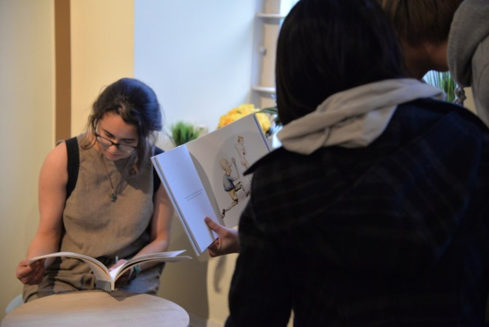 Visitors read 'Shit PopPop Says' on Thursday evening illustrated and designed by Allison Daigle, which is the final part of her BFA submission. (Amar Batra/The Daily Campus)