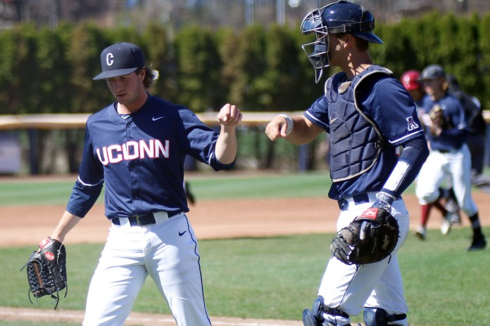 UConn pitcher P.J. Poulin bumps fists with his catcher during the Huskies 11-3 victory over UMass Amherst on Tuesday, April 18, 2017. (Ian Bethune/The UConn Blog)
