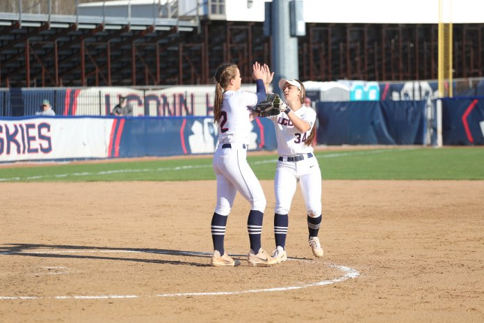 Jill Stockley (#2) and Kiwi McDaniel (#34) meet on the mound during their game against UMass. (Tyler Benton/The Daily Campus)