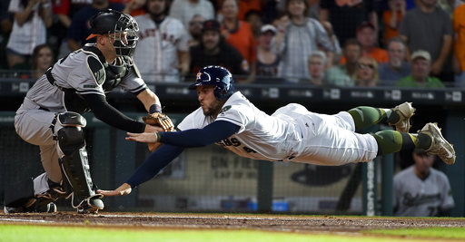 Houston Astros'George Springer, right, dives past Baltimore Orioles catcher Caleb Joseph (36) to score a run on Jose Altuve's RBI double during the first inning of a baseball game, Saturday, May 27, 2017, in Houston. (Eric Christian Smith/AP)