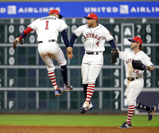 Houston Astros' Carlos Correa (1),George Springer (4) and Josh Reddick (22) celebrate after the team's baseball game against the New York Yankees on Saturday, July 1, 2017, in Houston. The Astros won 7-6. (AP Photo/David J. Phillip)
