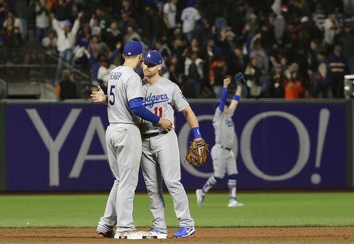 Los Angeles Dodgers' Corey Seager (5) celebrates with Logan Forsythe after the Dodgers defeated the San Francisco Giants 5-3 in a baseball game in San Francisco, Tuesday, Sept. 12, 2017. (AP Photo/Jeff Chiu)