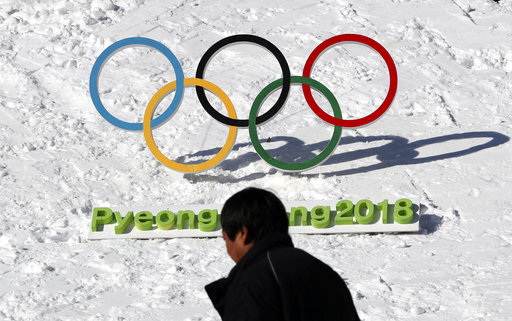 In this Feb. 3, 2017 photo, a man walks by the Olympic rings with a sign of 2018 Pyeongchang Olympic and Paralympic Winter Games in Pyeongchang, South Korea. With five months to go before the opening ceremony of the Pyeongchang Winter Olympics, organizers are desperate to sell more tickets in a country where the Games have failed to dominate national conversation amid an upheaval in domestic politics and a torrent of North Korean missile launches. (AP Photo/Lee Jin-man)