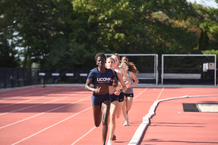 Part of the girls cross country team practices on the track to improve their speed. Many of the athletes in cross country continue their season into track and field. (Charlotte Lao/The Daily Campus)