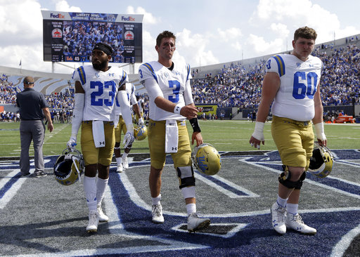 UCLA quarterback Josh Rosen (3), running back Nate Starks (23), and offensive lineman Zach Sweeney (60) leave the field after UCLA lost to Memphis 48-45 in an NCAA college football game Saturday, Sept. 16, 2017, in Memphis, Tenn. (AP Photo/Mark Humphrey)
