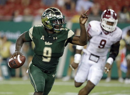 South Florida quarterback Quinton Flowers, left, runs past Temple defensive lineman Jacob Martin during the second half of an NCAA college football game Thursday, Sept. 21, 2017, in Tampa, Fla. (AP Photo/Chris O'Meara)