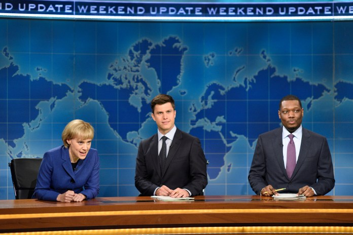 """In this image released by NBC, Kate McKinnon portraying German Chancellor Angela Merkel, left, appears with Weekend Update hosts Colin Jost, center, and Michael Che during their segment on """"Saturday Night Live,"""" in New York on Sept. 30, 2017. (Will Heath/NBC via AP)"""