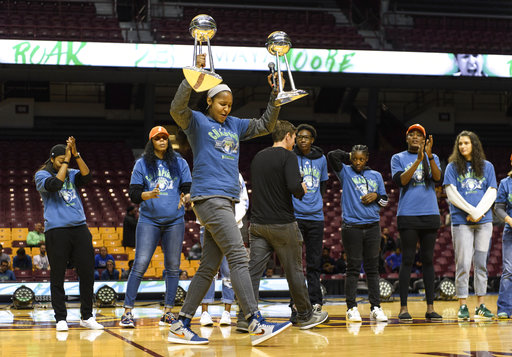 Minnesota Lynx forward Maya Moore holds two WNBA championship trophies before addressing the crowd at a victory rally, Thursday, Oct. 5, 2017, in Minneapolis. (Aaron Lavinsky/Star Tribune via AP)