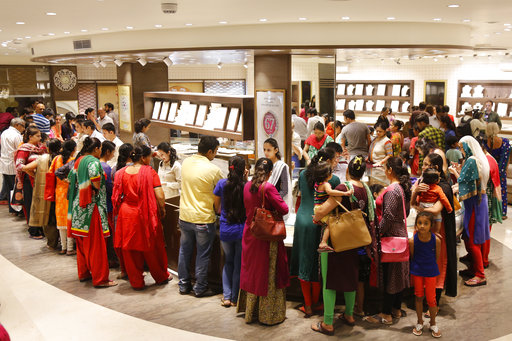 Indians crowd a jewelry shop on Guru Pushya Nakshatra in Ahmadabad,India, Friday, Oct. 13, 2017. The day is considered auspicious for buying gold, as per the Hindu calendar. (AP Photo/Ajit Solanki)