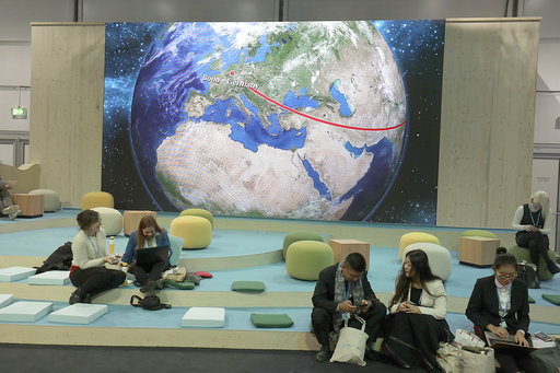 Participants at the World Climate Conference working in front of the depiction of a globe in Bonn, Germany, Tuesday, Nov. 7, 2017. (Oliver Berg/dpa via AP)