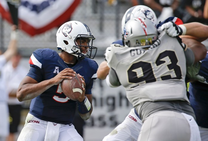 Connecticut quarterback David Pindell, left, looks for a receiver as he is pressured by Central Florida defensive lineman Tony Guerad (93) during the first half of an NCAA college football game, Saturday, Nov. 11, 2017, in Orlando, Fla. (AP Photo/John Raoux)