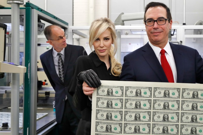 Treasury Secretary Steven Mnuchin, right, and his wife Louise Linton, hold up a sheet of new $1 bills, the first currency notes bearing his and U.S. Treasurer Jovita Carranza's signatures, Wednesday, Nov. 15, 2017. The Mnuchin-Carranza notes, which are a new series of 2017, 50-subject $1 notes, will be sent to the Federal Reserve to issue into circulation. (Jacquelyn Martin/AP)