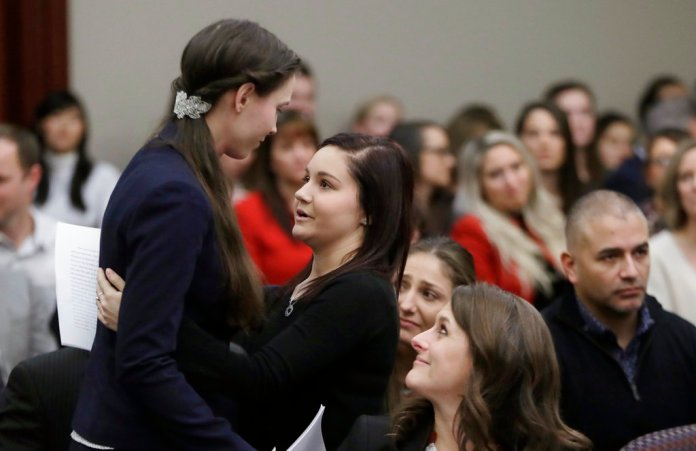 Former gymnast Rachael Denhollander, left, is hugged by Kaylee Lorincz after giving her victim impact statement during the seventh day of Larry Nassar's sentencing hearing Wednesday, Jan. 24, 2018, in Lansing, Mich.(AP Photo/Carlos Osorio)