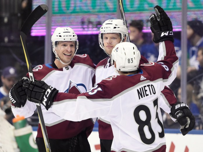 Colorado Avalanche left wing Blake Comeau (14) celebrates his goal with center Carl Soderberg (34) and left wing Matt Nieto (83) during third-period NHL hockey game action against the Toronto Maple Leafs in Toronto, Monday, Jan. 22, 2018. (Nathan Denette/The Canadian Press via AP)
