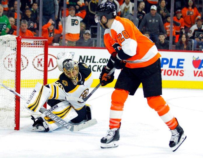 Philadelphia Flyers' Claude Giroux, right, scores past Boston Bruins goalie Anton Khudobin during overtime to win an NHL hockey game Sunday, April 1, 2018 in Philadelphia. The Flyers won 4-3. (AP Photo/Tom Mihalek)