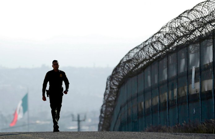 In this June 22, 2016 file photo, Border Patrol agent Eduardo Olmos walks near the secondary fence separating Tijuana, Mexico, background, and San Diego in San Diego. (AP Photo/Gregory Bull, File)