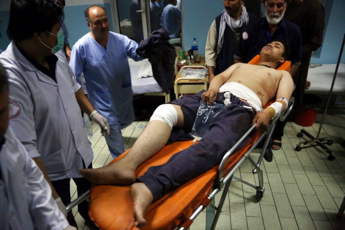 An injured man is brought in to a hospital following a deadly attack in Kabul, Afghanistan, Wednesday, Sept. 5, 2018. Twin bombings at a wrestling training center in a Shiite neighborhood of Afghanistan's capital on Wednesday killed at least 20 people, Afghan officials said. (AP Photo/Rahmat Gul)