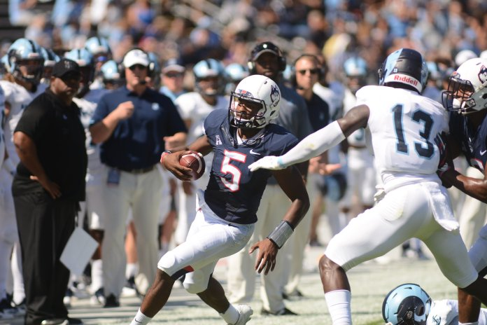 Quarterback David Pindell navigates the sideline during UConn's 56-49 win over URI on Sept. 15, 2018. (Eric Wang/ The Daily Campus)