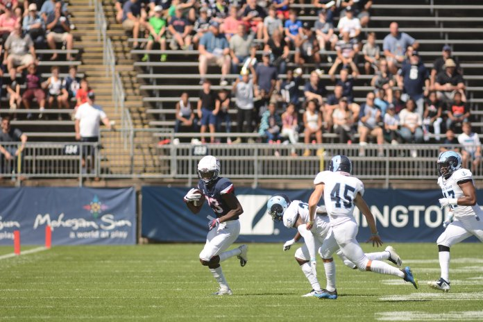 UConn wide receiver Keyion Dixon tries to break free from URI defenders during a game on Sept. 15, 2018. (Eric Wang/ The Daily Campus)