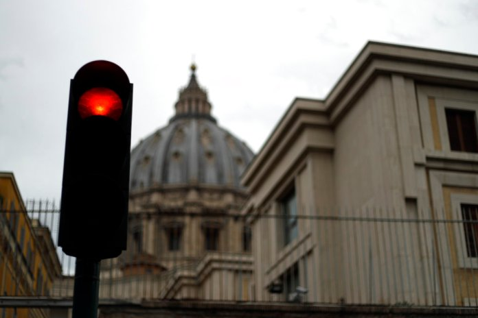 A traffic light is seen outside the Perugino Gate at the Vatican, Thursday, Sept. 13, 2018. A delegation of U.S. Catholic cardinals and bishops met Thursday with Pope Francis amid a crisis of confidence in church leadership following new sex abuse and cover-up revelations that have also implicated Francis himself. (AP Photo/Gregorio Borgia)