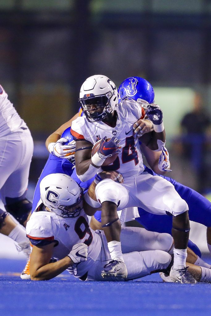 Connecticut running back Kevin Mensah center tries to spin away from Boise State defense in the second half of an NCAA college football game, Saturday, Sept. 8, 2018, in Boise, Idaho. Boise State won 62-7. (AP Photo/Steve Conner)