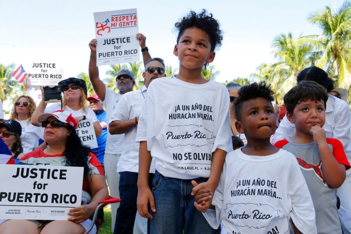 Hector Rivera, 8, Mario Jordan Micael, 3, and Ramon Montes, 5, participate in a rally in West Palm Beach, Fla., on Saturday, Sept. 22, 2018, marking the one-year anniversary of Hurricane Maria's devastation of Puerto Rico. (AP Photo/Ellis Rua)