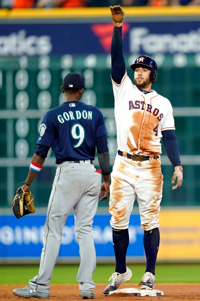 Houston Astros' George Springer (4) celebrates after a RBI single as Seattle Mariners second baseman Dee Gordon (9) watches during the third inning of a baseball game Tuesday, Sept. 18, 2018, in Houston. (AP Photo/David J. Phillip)