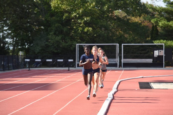 Part of the girls cross country team practices on the track to improve their speed. Many of the athletes in cross country continue their season into track and field. (Photo by Charlotte Lao/The Daily Campus)