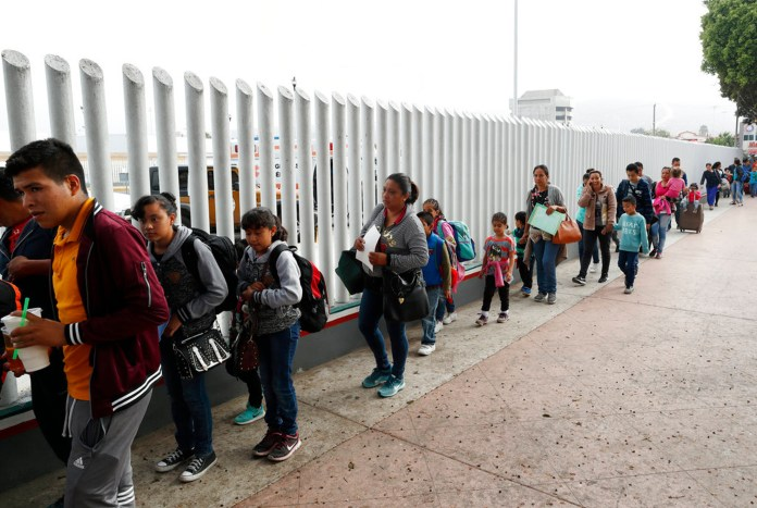"""FILE - This July 26, 2018, file photo shows people lining up to cross into the United States to begin the process of applying for asylum near the San Ysidro port of entry in Tijuana, Mexico. Homeland Security's watchdog says immigration officials were not prepared to manage the consequences of its """"zero tolerance"""" policy at the border this summer that resulted in separation of nearly 3,000 children from parents. (AP Photo/Gregory Bull, File)"""