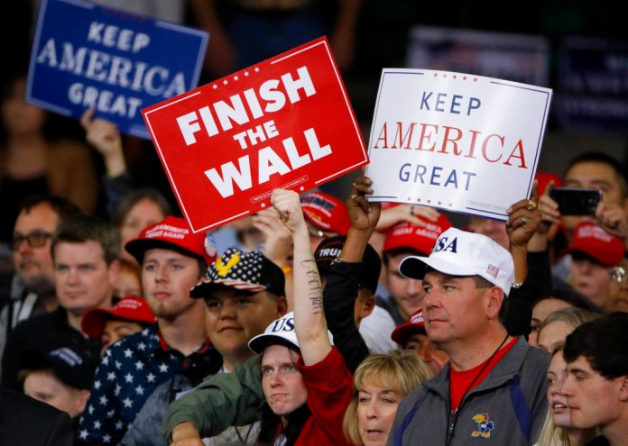 People watch as President Donald Trump addresses the crowd during a campaign rally Saturday, Oct. 6, 2018, in Topeka, Kan. (AP Photo/Charlie Riedel)