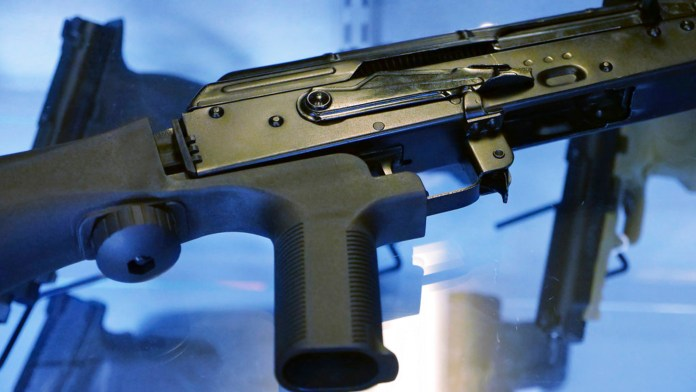 """FILE - This Oct. 4, 2017 file photo shows a device called a """"bump stock"""" attached to a semi-automatic rifle at a gun store and shooting range in Utah. What's happened to bump stocks in the year since Las Vegas? There were growing calls to ban the devices in the immediate aftermath of the mass shooting on the Las Vegas strip. Some succeeded, but others did not. (AP Photo/Rick Bowmer, File)"""