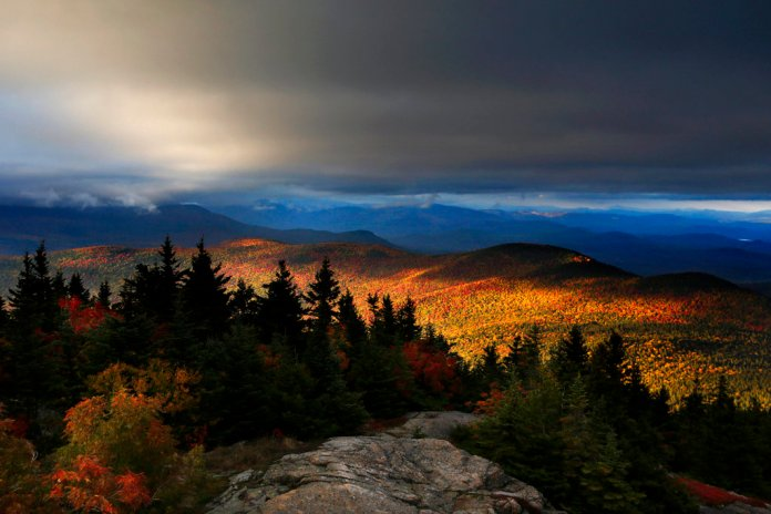 FILE - In this Oct. 4, 2016, file photo, fall foliage colors a line of mountains in Chatham, N. H. For a different perspective on the fall foliage, try viewing the colors from the summit of a New England peak, either by hiking, driving or taking a ski lift. (AP Photo/Robert F. Bukaty, File)