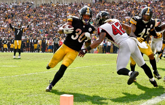 Pittsburgh Steelers running back James Conner (30) takes a handoff from quarterback Ben Roethlisberger (7) and runs it in for a touchdown around Atlanta Falcons linebacker Duke Riley (42) in the second half of an NFL football game against the Pittsburgh Steelers, Sunday, Oct. 7, 2018, in Pittsburgh. (AP Photo/Don Wright)
