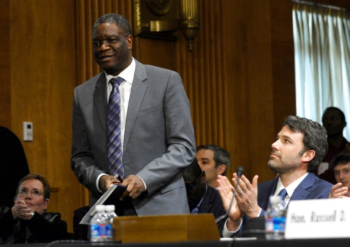 """FILE - In this Wednesday, Feb. 26, 2014 file photo, actor and Eastern Congo Initiative Founder Ben Affleck, right, applauds Dr. Denis Mukwege, founder of Panzi Hospital in the Democratic Republican of the Congo, on Capitol Hill in Washington. The Nobel Peace Prize has been awarded to Denis Mukwege and Nadia Murad """"for their efforts to end the use of sexual violence as a weapon of war and armed conflict, """" it was announced on Friday, Oct. 5, 2018. (AP Photo/Susan Walsh, file)"""