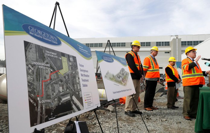 Andrew Wheeler, right, the U.S. Environmental Protection Agency's Acting Administrator, talks to reporters, Wednesday, Oct. 3, 2018, after touring the Georgetown Wet Weather Treatment Station in Seattle, a project funded by a low-interest loan from the EPA. The facility will treat millions of gallons of polluted stormwater that currently flows into Duwamish River during severe rainstorms. (AP Photo/Ted S. Warren)
