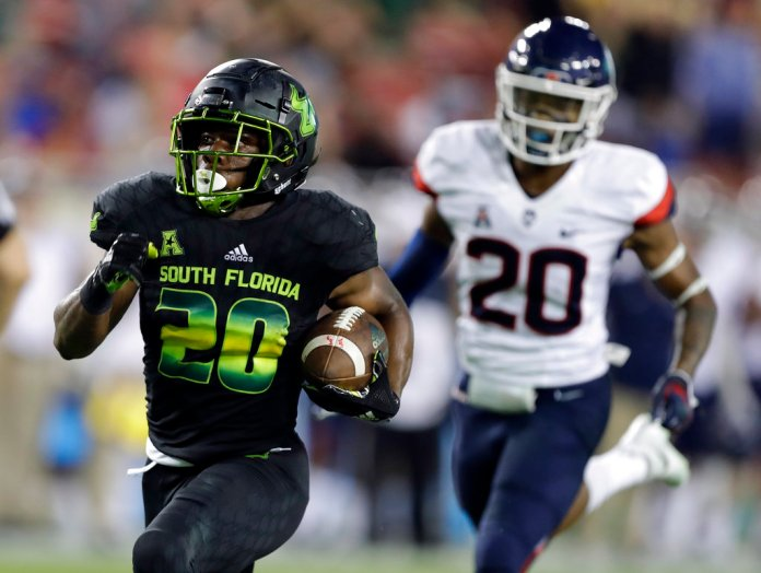 South Florida running back Johnny Ford, left, outruns Connecticut defensive back Robert P. King III on a 43-yard touchdown run during the second half of an NCAA college football game Saturday, Oct. 20, 2018, in Tampa, Fla. (AP Photo/Chris O'Meara)