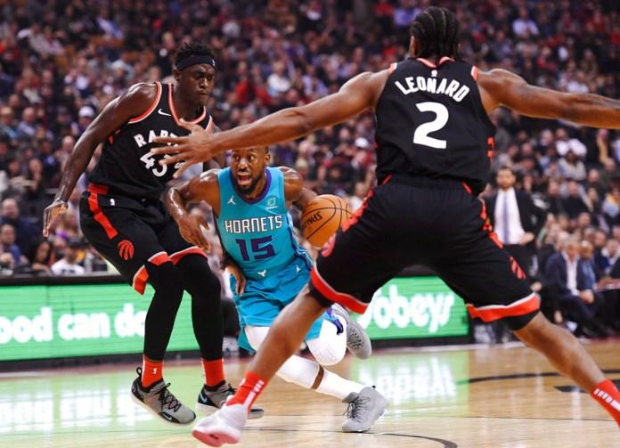Charlotte Hornets guard Kemba Walker (15) drives between Toronto Raptors forwards Pascal Siakam (43) and Kawhi Leonard (2) during first-half NBA basketball game action in Toronto, Monday, Oct. 22, 2018. (Nathan Denette/The Canadian Press via AP)