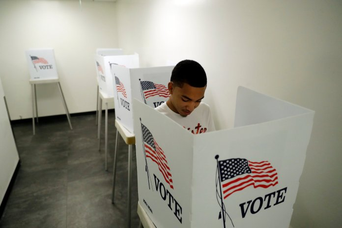 Christian Goodman, 18, votes for the first time in his life at the Los Angeles County Registrar of Voters office Tuesday, Oct. 23 in Norwalk, Calif. The general election takes place on Nov. 6. (Marcio Jose Sanchez/AP)