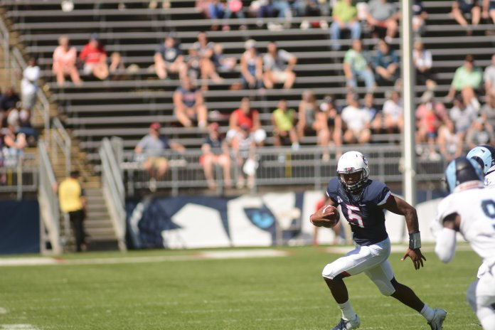 Quarterback David Pindell scrambles during a game against URI on Sept. 15, 2018. (Eric Wang/ The Daily Campus)
