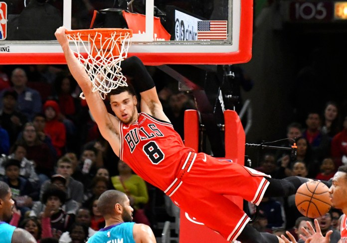 Chicago Bulls guard Zach LaVine (8) hangs on the rim after dunking the ball against the Charlotte Hornets during the second half of a NBA basketball game Wednesday, Oct. 24, 2018, in Chicago. The Bulls won 112-110. (AP Photo/David Banks)