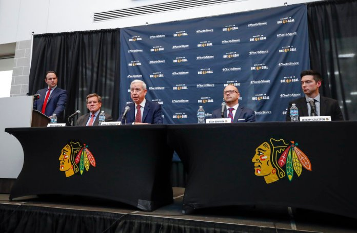 Chicago Blackhawks President and CEO John McDonough, center, speaks during an NHL hockey press conference to announce hiring Jeremy Colliton, right, as a Blackhawks new head coach Tuesday, Nov. 6, 2018, in Chicago. Colliton replaces Joel Quenneville who was fired on Tuesday. (AP Photo/Kamil Krzaczynski)