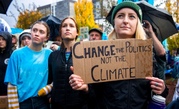 Willamette University student Arabella Wood, right, gathers with others at a rally in Eugene, Ore., Monday, Oct. 29, 2018, to support a high-profile climate change lawsuit brought by 21 young people against the federal government. Trial was set to begin in federal court in Eugene Monday morning. But the U.S. Supreme Court temporarily halted the proceedings to decide whether the case should move forward. (Andy Nelson/The Register-Guard via AP)