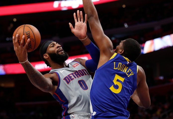 Detroit Pistons center and former UConn player Andre Drummond (0) shoots as Golden State Warriors forward Kevon Looney (5) defends during a game on Saturday, Dec. 1 in Detroit. (Carlos Osorio/AP)