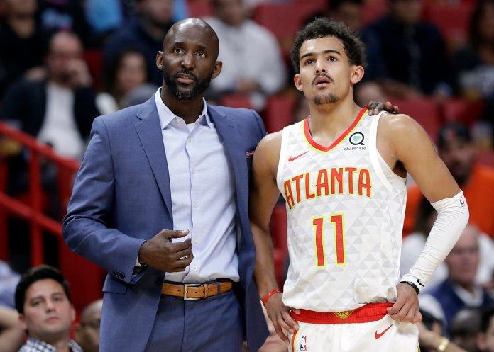 Atlanta Hawks head coach Lloyd Pierce, left, talks with guard Trae Young during a game against the Miami Heat on Tuesday, Nov. 27 in Miami. (Lynne Sladky/AP)