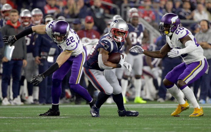 New England Patriots running back James White, center, runs from Minnesota Vikings defenders during a game on Sunday, Dec. 2 in Foxborough. (Steven Senne/AP)