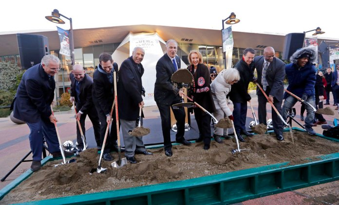 Gov. Jay Inslee, center left, tosses a chunk of frozen sand as Seattle Mayor Jenny Durkan looks on from his left and former Seattle SuperSonics head coach Lenny Wilkens stands on his right with other officials during a ceremonial groundbreaking of a renovation of the arena at Seattle Center Wednesday, Dec. 5, 2018, in Seattle. The NHL Board of Governors gave final approval to Seattle's bid to add the hockey league's 32nd team a day earlier and play is expected to begin at the arena in 2021. (AP Photo/Elaine Thompson)
