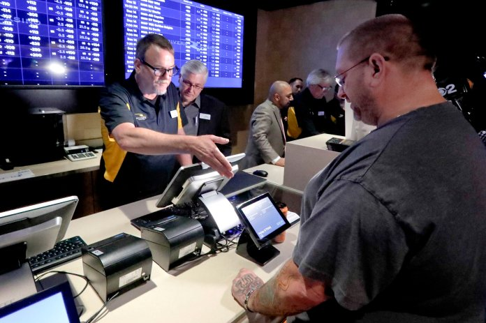 In this Dec. 13, 2018, file photo, Ryan Martin, right, looks over his wager at Rivers Casino, as the new, temporary sports betting area opened in Pittsburgh. Pending Pennsylvania Gaming Control Board approval, regular operations are scheduled to begin Saturday, Dec. 15. Marton made several wagers, including placing a $100 bet on the Pittsburgh Steelers to win the Super Bowl. Anyone willing to wager that the high-scoring Patriots or Rams will get shut out in the Super Bowl can count on a big payday if that unlikely scenario occurs. Prop bets aren't a big moneymaker for sports books during the season, but they pick up popularity as the nation is intensely focused on a single game. (AP Photo/Keith Srakocic. File)