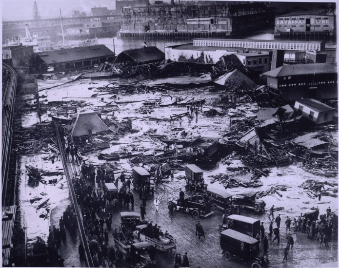 Twenty one people were killed on Commercial Street in the North End when a tank of molasses ruptured and exploded. An eight foot wave of the syrupy brown liquid moved down Commercial Street at a speed of 35mph. Wreckage of the collapsed tank visible in background, center, next to light colored warehouse. Elevated railway structure visible at far left and the North End Park bathing beach to the far right.(Flickr/Creative Commons)